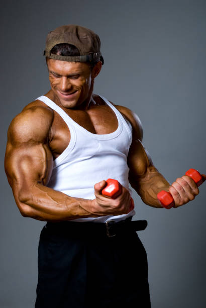 Muscular man training with small dumbbells stock photo