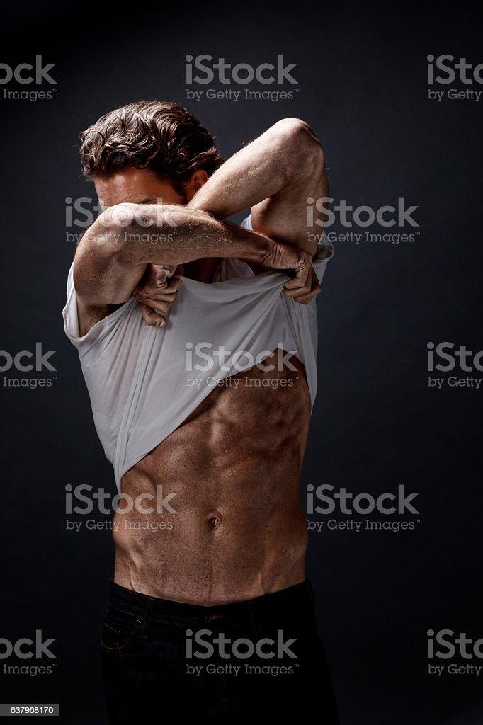 Muscular man undressing stock photo