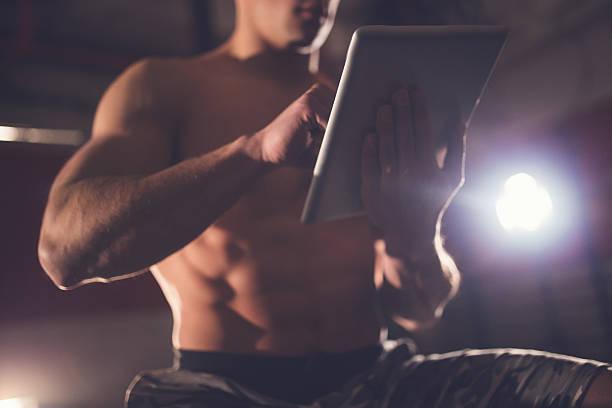 muskel mann verwendet tablet im fitnessraum - trainingstagebuch stock-fotos und bilder