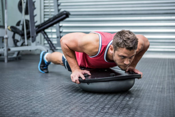 Muscular man using bosu ball stock photo