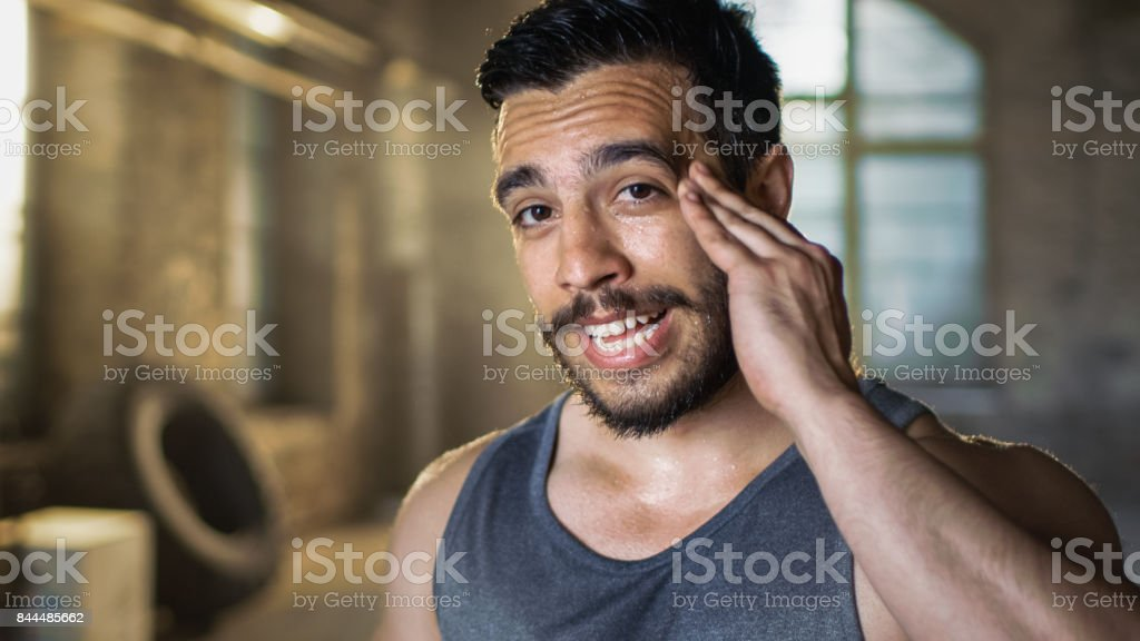 Muscular Man Wipers Sweat of His Forehead after Intensive Cross Fitness Bodybuilding Training. He Smiles Charmingly. He Wears Sleeveless Shirt and Works out in a Gym. stock photo