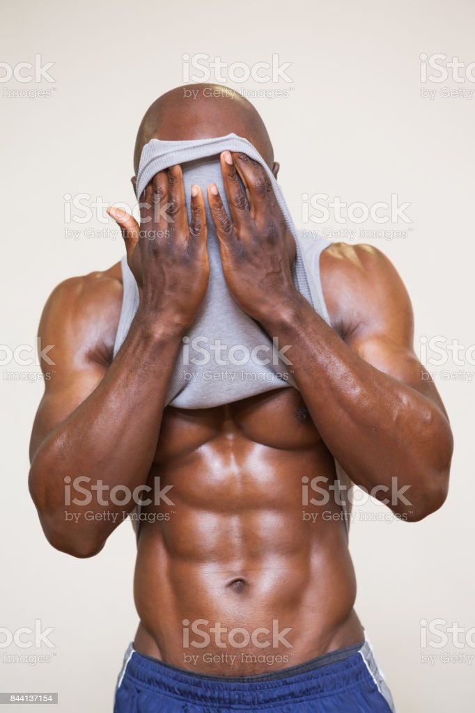 Muscular man wiping sweat after workout stock photo