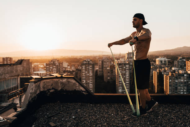 Muscular man with a resistance band exercising outdoors stock photo