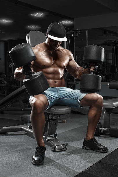 muscular man con gran mancuernas de ejercitarse en el gimnasio - hombres grandes musculosos fotografías e imágenes de stock