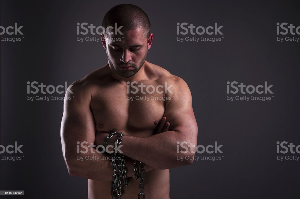 Muscular man with chain wraped around his arm royalty-free stock photo