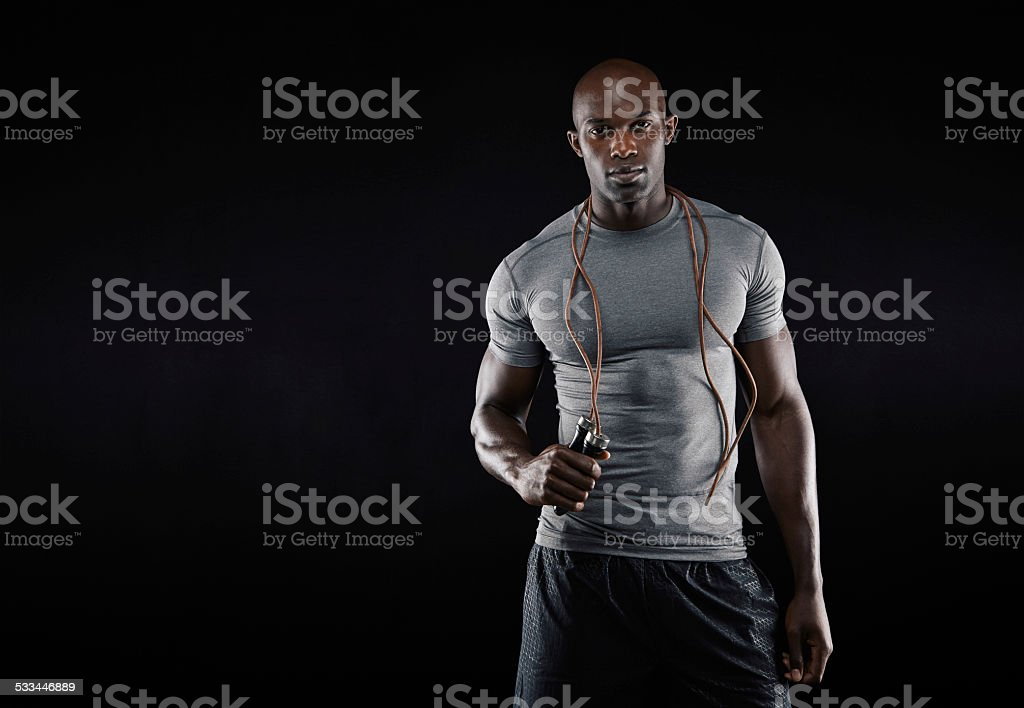 Muscular man with jumping rope stock photo