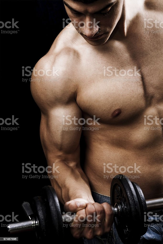 A muscular man with no shirt on lifting a weight royalty-free stock photo