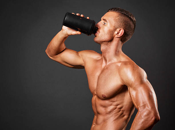 Muscular man with protein drink in shaker stock photo