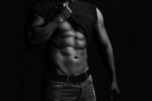 Muscular man with shirt on shoulder One handsome sexual strong young man with muscular body in jeans with shirt on shoulder standing posing on studio background black and white, horizontal picture shirtless male models stock pictures, royalty-free photos & images