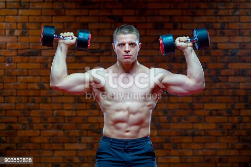 908985656 istock photo Muscular man working doing exercises with dumbbells, strong male naked torso abs on the background of red brick wall 903552828