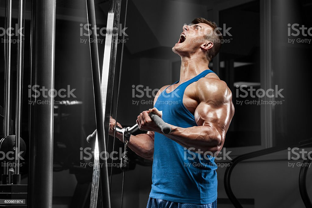 Muscular man working out in gym doing exercises at biceps - foto de acervo