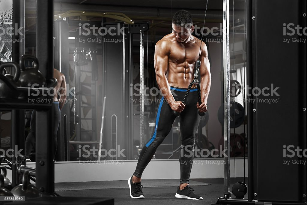 Muscular man working out in gym doing exercises at triceps stock photo