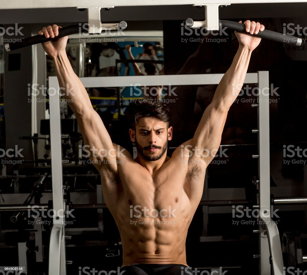Muscular man working out in gym doing exercises at triceps royalty-free stock photo
