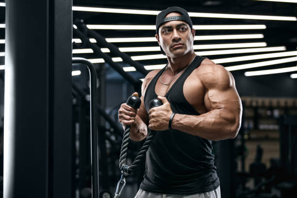 Muscular man working out in gym doing exercises for biceps. Strong male stock photo