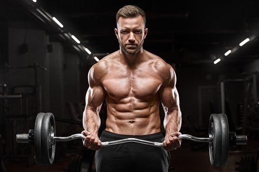 Muscular Man Working Out In Gym Doing Exercises On