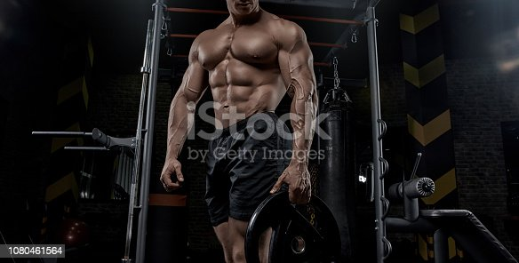 istock Muscular man working out in gym doing exercises. 1080461564