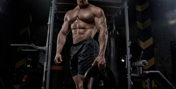 hombre trabajando en el gimnasio haciendo ejercicios. - culturismo fotografías e imágenes de stock