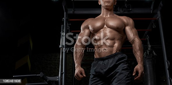 618638418istockphoto Muscular man working out in gym doing exercises. 1080461606