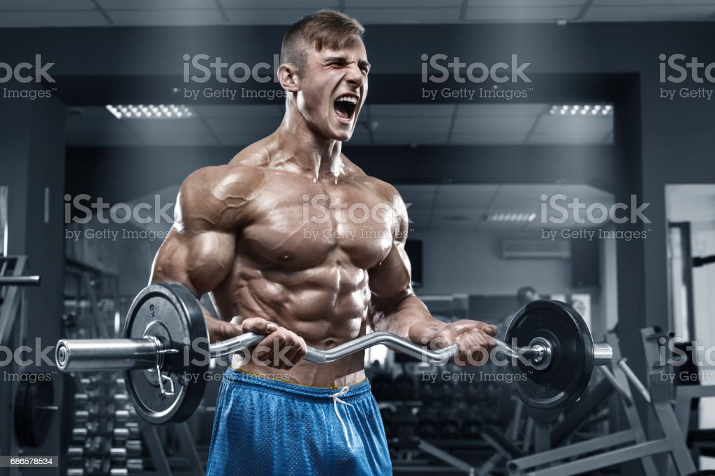 Muscular man working out in gym doing exercises, strong male naked torso abs foto stock royalty-free