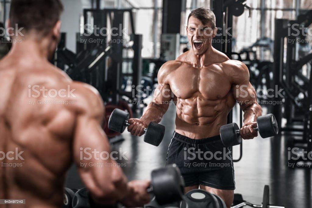 Gespierde man trainen in de sportschool doen oefeningen, sterke mannelijke naakte torso abs foto
