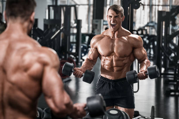 Muscular man working out in gym doing exercises, strong male naked torso abs stock photo