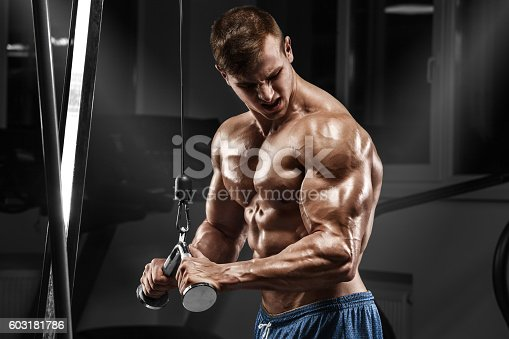 istock Muscular man working out in gym doing exercises, torso abs 603181786