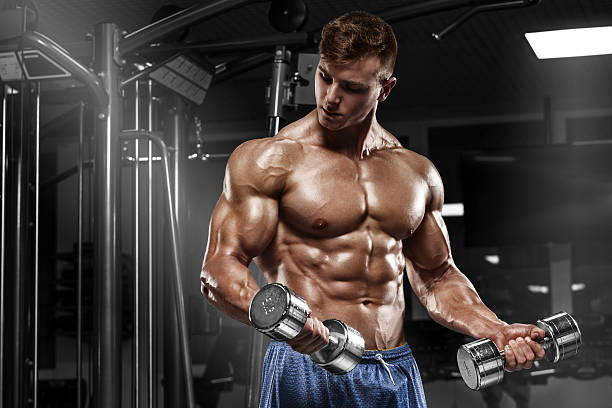 Muscular man working out in gym doing exercises, torso abs stock photo