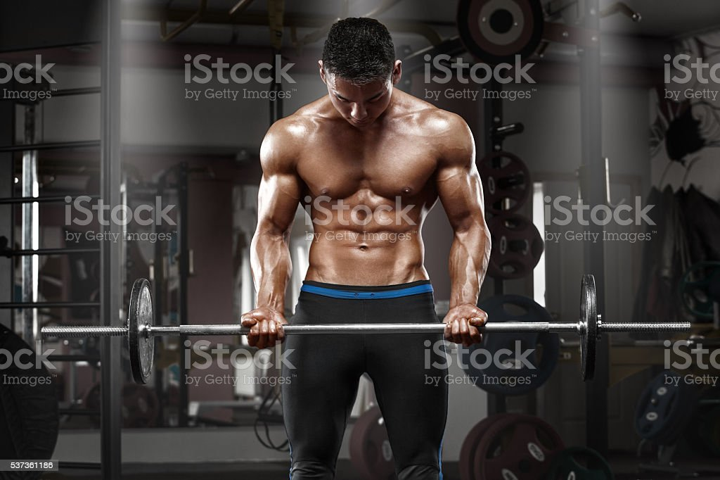 Muscular man working out in gym doing exercises with barbell stock photo