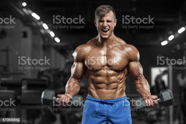 Muscular Man Working Out In Gym Doing Exercises With