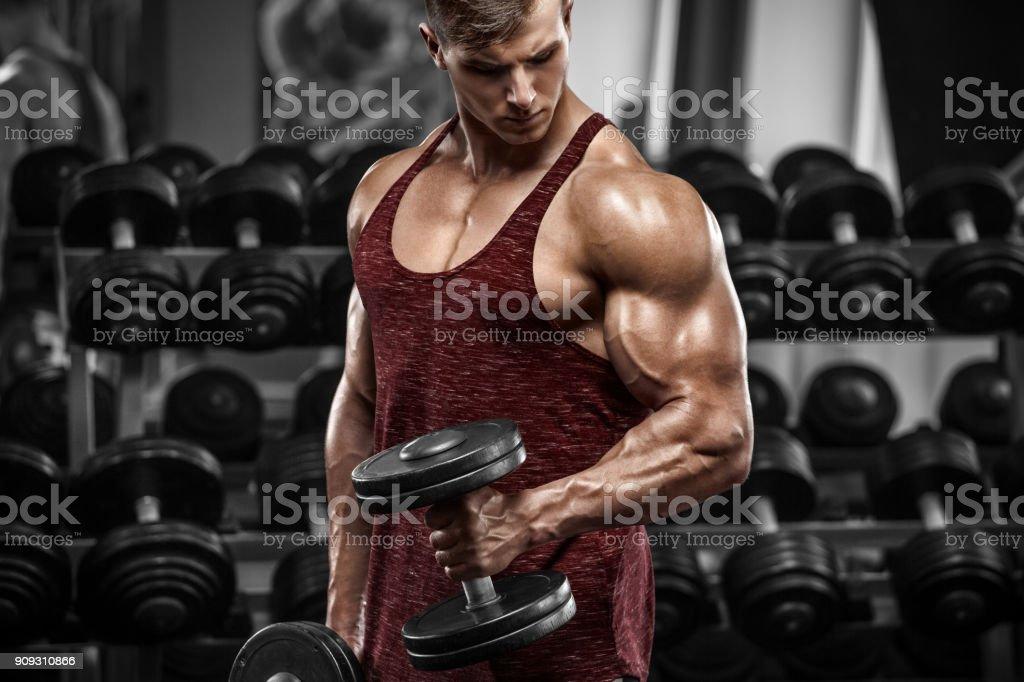Gespierde man trainen in de sportschool doen oefeningen met halters, sterke man foto