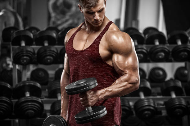 Muscular man working out in gym doing exercises with dumbbells, strong male stock photo