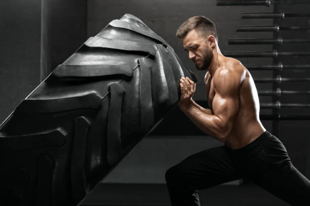 hombre trabajando en gimnasio bancos neumático, fuerte torso desnudo masculino - entrenamiento con pesas fotografías e imágenes de stock