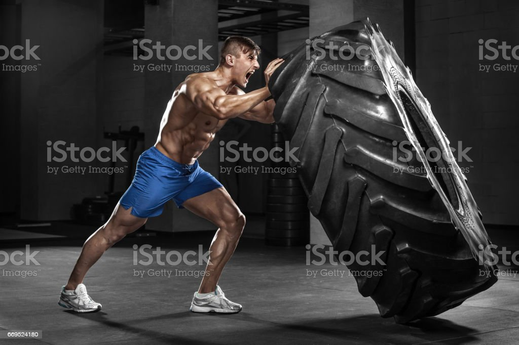 Muscular man working out in gym flipping tire, strong male naked torso abs stock photo