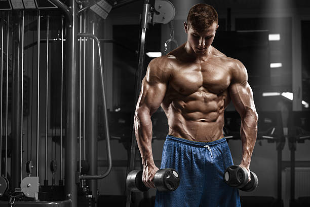 Muscular man working out in gym, male naked torso abs stock photo