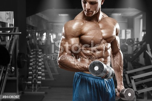 istock Muscular man working out in gym. Strong male torso abs 494436262