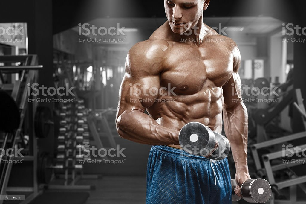 Muscular man working out in gym. Strong male torso abs stock photo