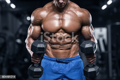 Muscular man working out in gym, strong male torso abs