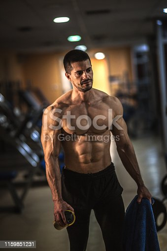 Muscular man working out in gym, strong male torso