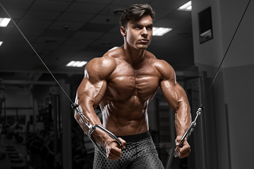Muscular man workout in gym doing exercises for chest, cable crossover. Strong male naked torso abs