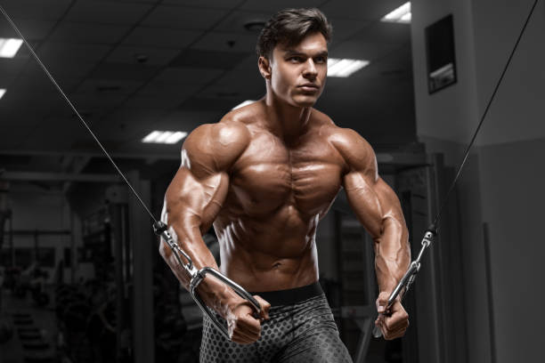Muscular man workout in gym doing exercises for chest, cable crossover. Strong male naked torso abs stock photo