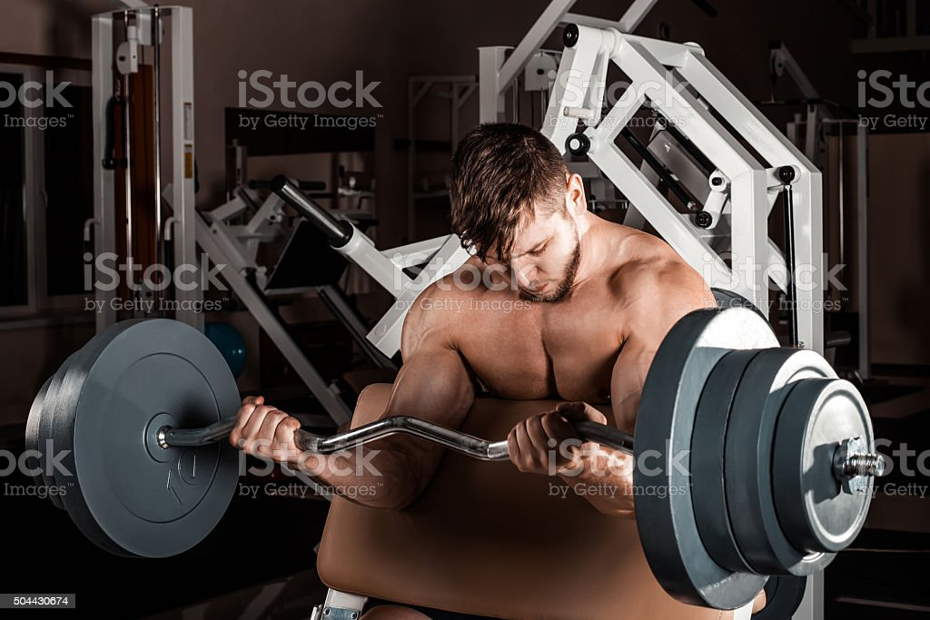 Muscular man workout with barbell stock photo