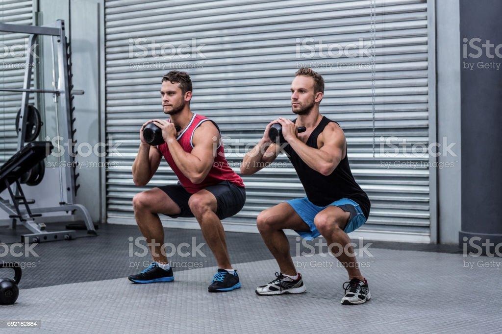 Muscular men exercising with kettlebells stock photo