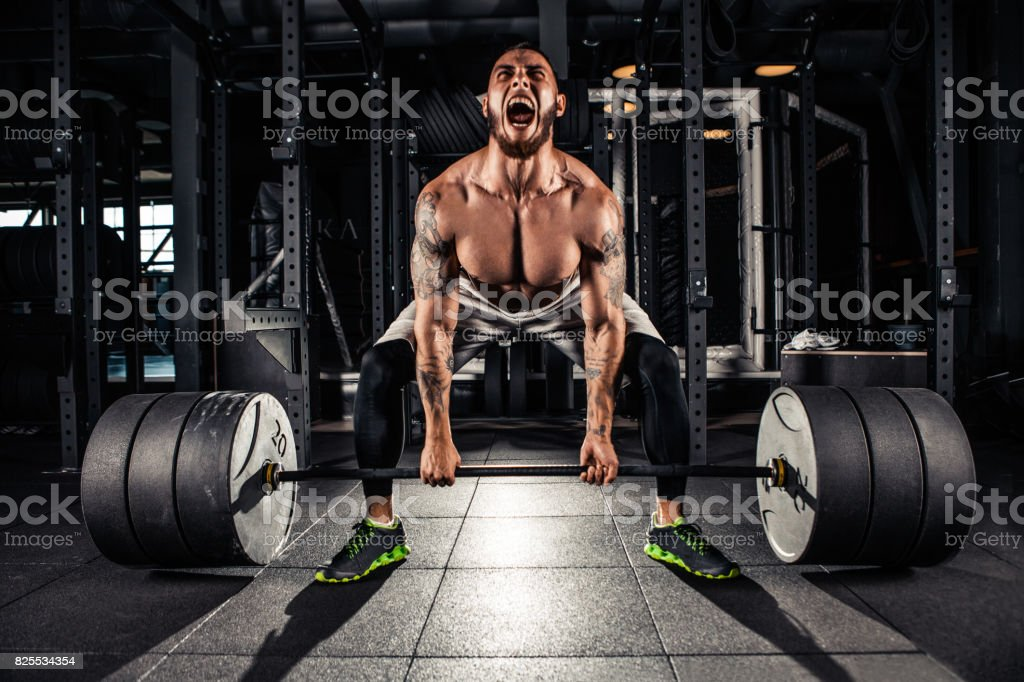 Muscular men lifting deadlift stock photo