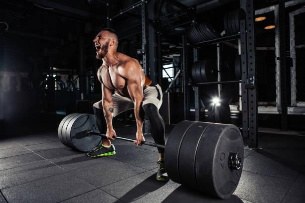 Muscular men lifting deadlift stock photo