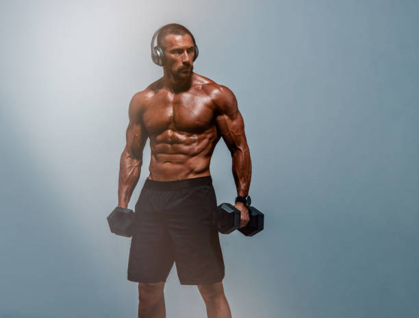 Muscular Men Lifting Weights. Wearing Headphones and listen music during his workout stock photo