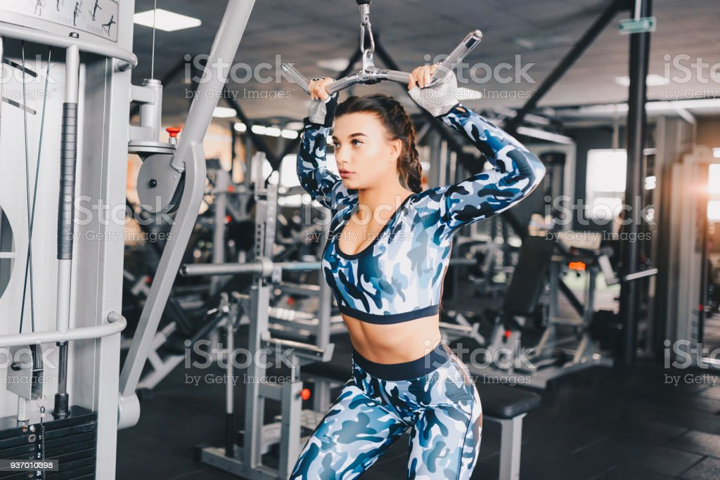 Muscular sexy young woman doing exercises on the simulator in the gym. Fitness, workout bodybuilding health care concept. stock photo