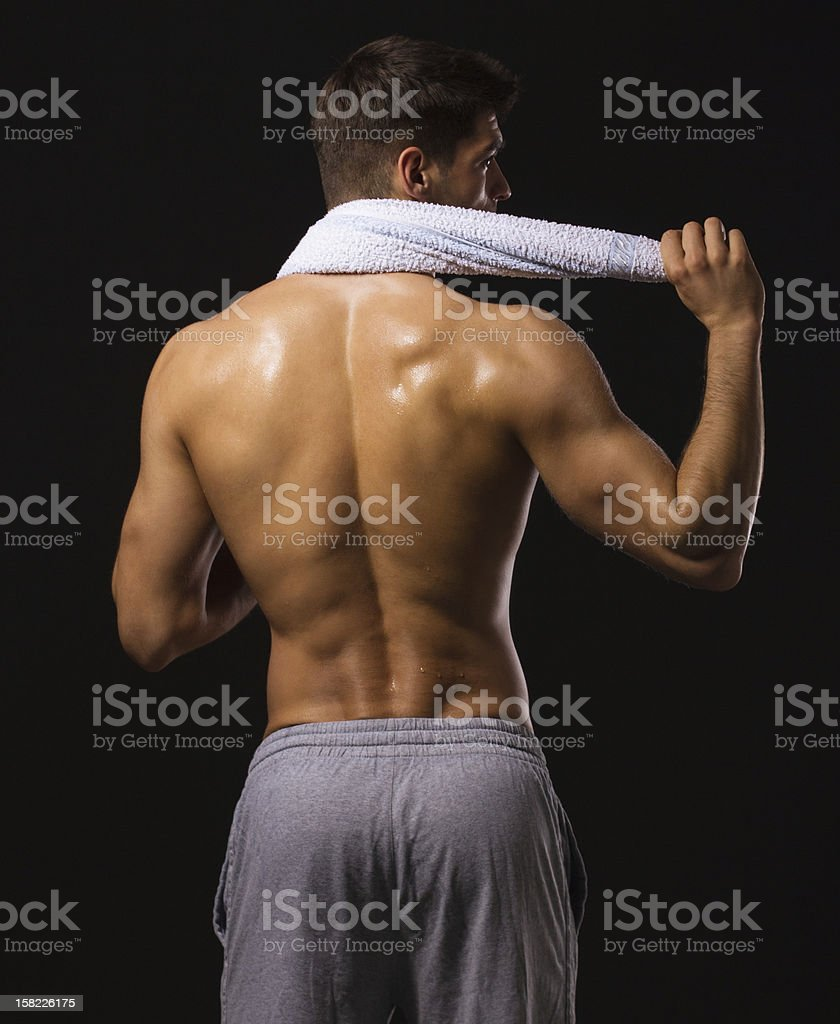 Muscular shirtless man from the back with towel royalty-free stock photo