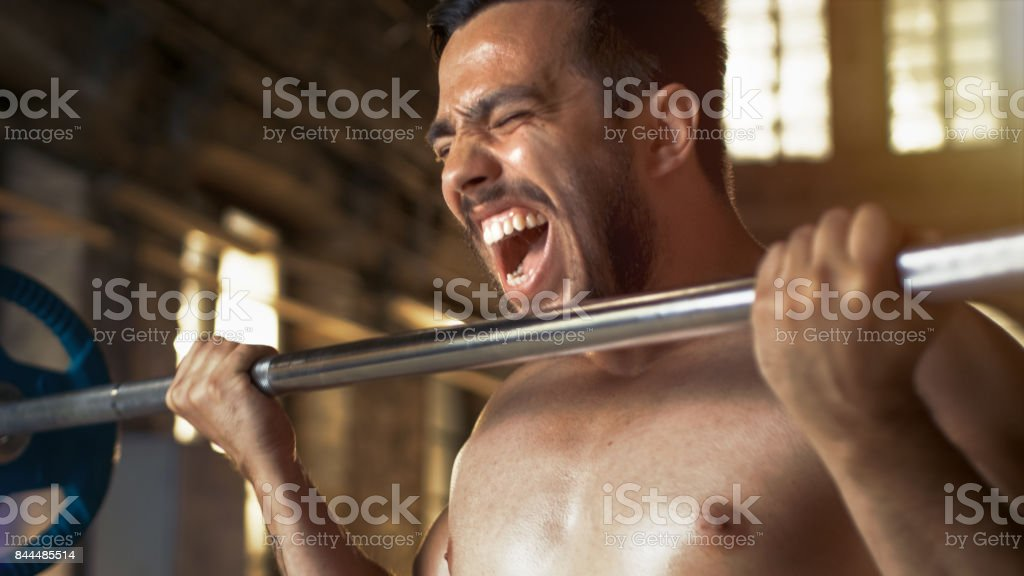 Muscular Shirtless Man Lifting Heavy Barbell with Effort, Doing...