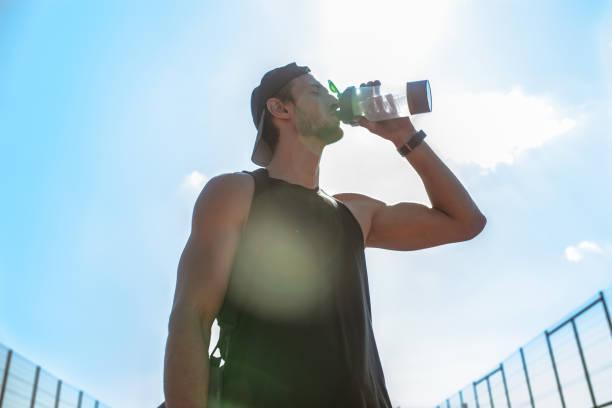 Muskulöse Sportler Trinkwasser im freien – Foto