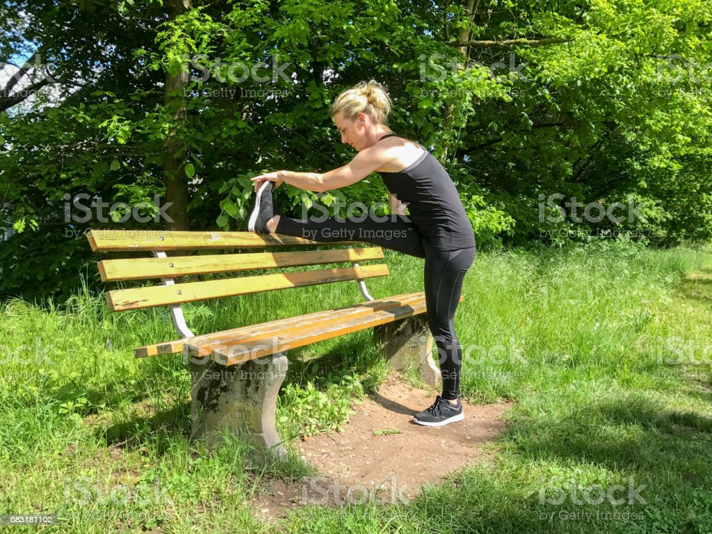 Muscular sporty woman limbering up in a park stock photo